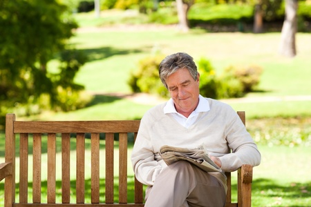 sitting on bench: Man reading a newspaper