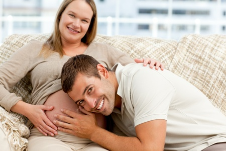 Smiling future dad listening to the belly of his wife sitting on the sofa Stock Photo - 10184739