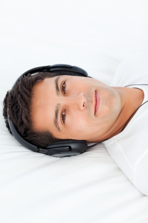 Serious man with headphones on lying on his bed photo