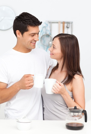 Adorable couple holding cups of coffee and looking at each other at breakfast photo