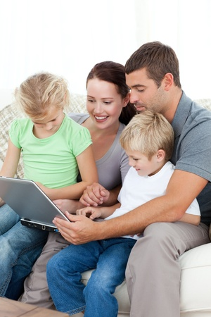 Parents and children using their laptop together sitting on the sofa Stock Photo - 10197281