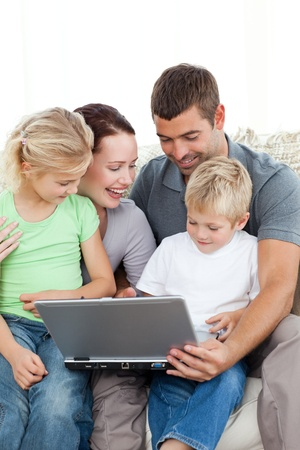 Adorable family working together on a laptop sitting on the sofa photo