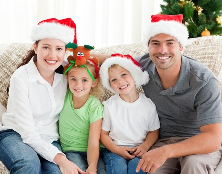 Portrait of a happy family with Christmas hats sitting on the sofa photo