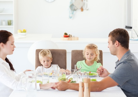Family praying together before eating their salad for lunch photo