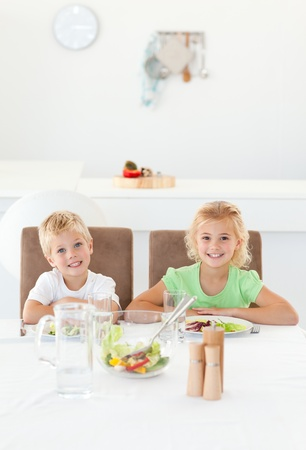 Adorable siblings eating a salad together in the kitchen photo
