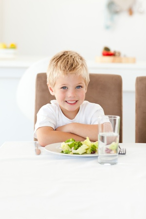 Cute little boy ready to eat his salad for lunch sitting at a table photo