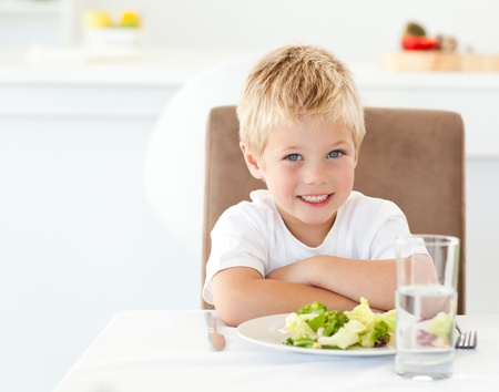 Portrait of a little boy eating a healthy salad for lunch photo