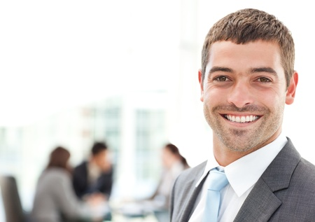 Businessman smiling at the camera while his team is working photo