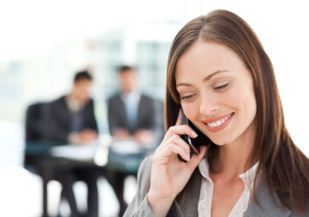 Pretty businesswoman on the phone while her team is working  photo