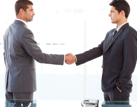 Serious businessmen shaking their hands after a meeting photo