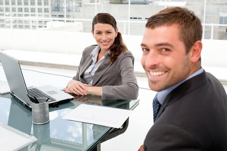 Happy businesspeople working together on a laptop during a meeting photo