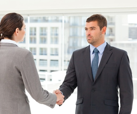 Two charismatic businesspeople shaking their hands photo