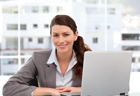 segretario: Donna sorridente sul computer guardando la fotocamera