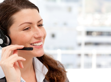 Smiling businesswoman talking on the phone with headphones photo