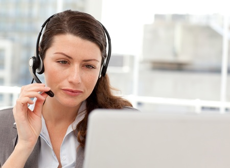 Concentrated businesswoman working on her laptop while calling photo