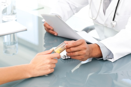 Close up of a doctor giving drugs to his patient during an appointment photo