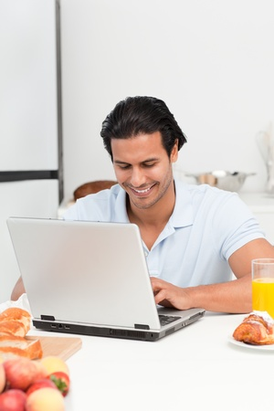Cheerful man working on his laptop during snack time photo