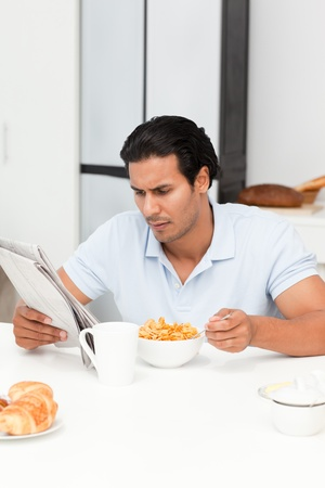 Serious man reading the newspaper while eating cereals photo