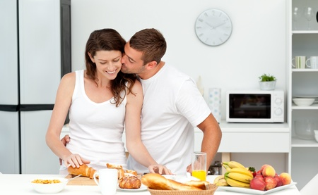 Affectionate man kissing his girlfriend while cutting bread for breakfast photo
