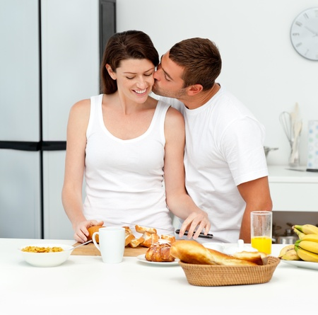 breakfast table: Passionate man kissing his girlfriend while cutting bread for breakfast Stock Photo