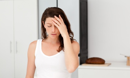 bother: Exhausted woman having a headache in her bathroom Stock Photo