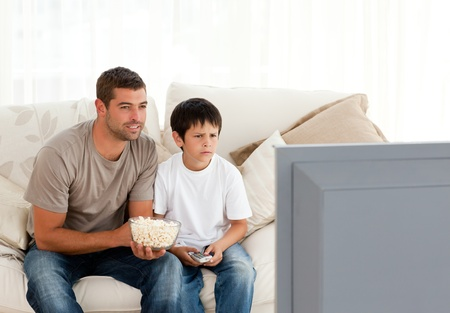 Concentrated father and son watching television while eating pop corn photo