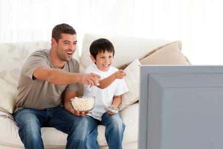 viewing: Felice padre e figlio, guardando la televisione mentre si mangia pop corn  Archivio Fotografico