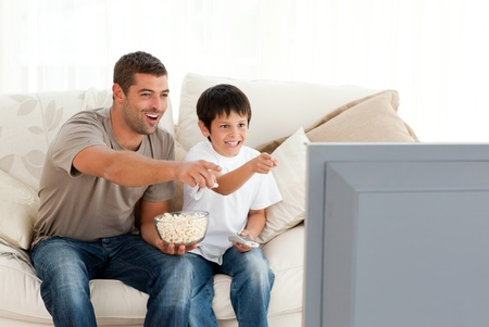 watching TV: Happy father and son watching television while eating pop corn  Stock Photo