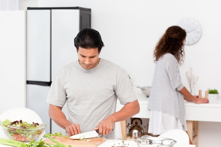 Hispanic couple preparing a salad together in the kitchen  photo