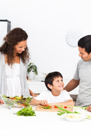 Happy family cutting vegetables together in the kitchen photo
