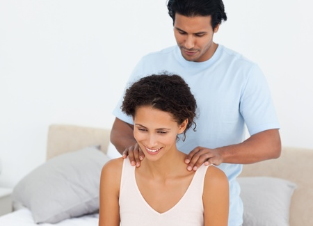 Handsome man doing a massage to his beautiful wife on their bed  photo