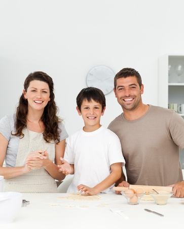 Cute boy with his parents in his kitchen photo