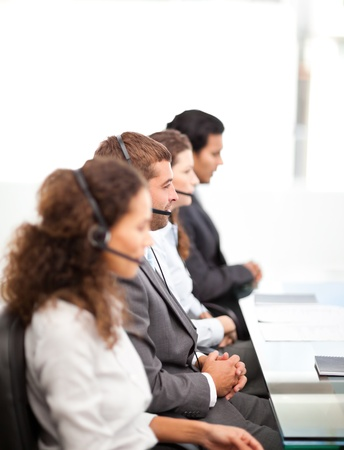 Four businesspeople on the phone sitting at their desk Stock Photo - 10196608