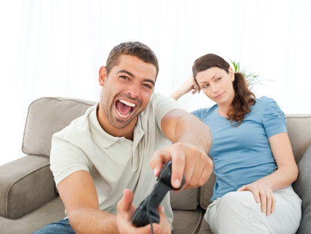 Pretty woman waiting for her boyfrind playing video games on the sofa Stock Photo - 10195546
