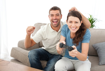 Cheerful man encouraging his girlfriend playing video game Stock Photo - 10191628