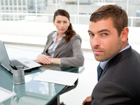 Serious businesspeople sitting around a table and looking at the camera photo