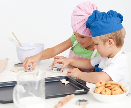 Cute sibling baking cookies together in the kitchen Stock Photo - 10196731