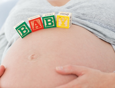 Close up of a pregnant woman with baby letters on her belly photo