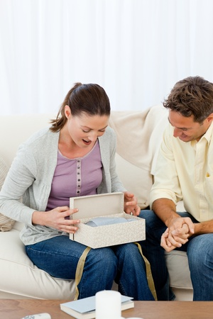 Amazed woman opening a present from his boyfriend on the sofa Stock Photo - 10184890