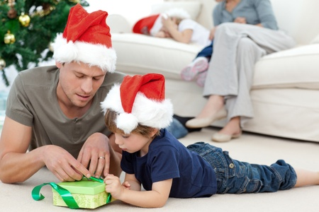 Father and son unwrapping a present lying on the floor photo