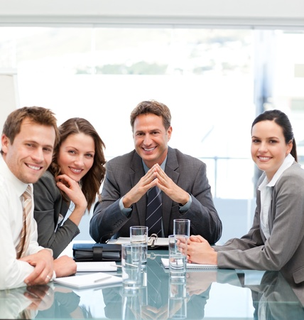 company employee: Portrait of a positive manager with his team sitting at a table Stock Photo