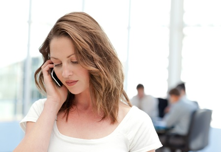 conference call: Businesswoman on the phone while her team is working