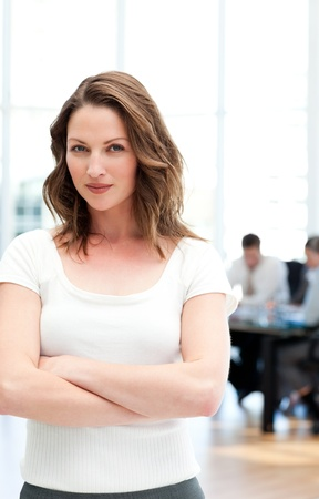 Proud businesswoman standing in front of her team while working photo