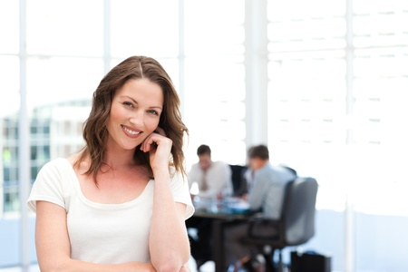 Cute businesswoman standing in front of her team while working Stock Photo - 10184143