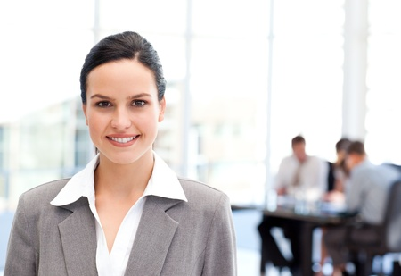 chairman: Adorable businesswoman standing in front of her team while working