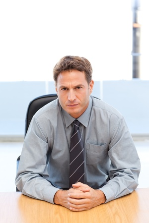 Confident manager posing alone at a table Stock Photo - 10197056