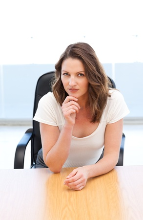 Pensive businesswoman sitting at a table photo