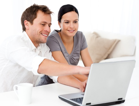 Cute man showing something on the laptop screen to his girlfriend photo