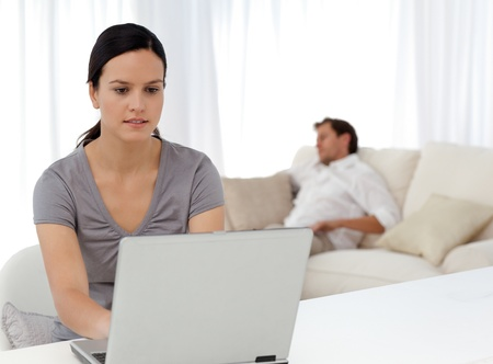 Attentive woman working on the laptop while her boyfriend is sleeping Stock Photo - 10182308