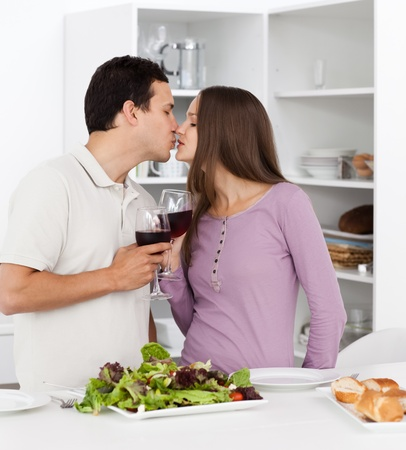 Cute couple kissing while having lunch in the kitchen photo